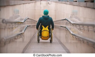 Disabled man in wheelchair getting down the long special ramp. Mid shot