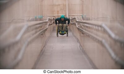 Disabled man in wheelchair getting up on the long special ramp. Mid shot