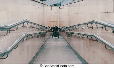 Disabled man in wheelchair getting up on the long special ramp with an effort. Mid shot