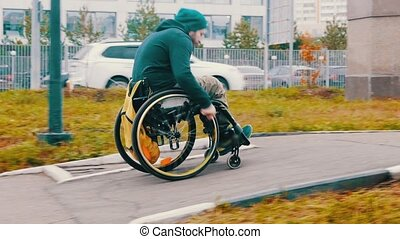 Disabled man in wheelchair makes a successful attempt to steer his wheelchair over a ramp on the street. Mid shot