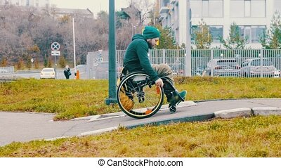 Disabled man in wheelchair makes attempt to steer his wheelchair over a ramp on the street but rolling back. Mid shot