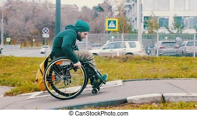 Disabled man in wheelchair makes attempt to steer his wheelchair over a ramp on the street. Mid shot