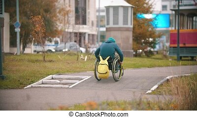 Disabled man in wheelchair makes failed attempt to steer his wheelchair over a ramp. Mid shot