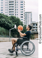 disabled man in wheelchair playing basketball