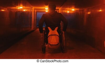 Disabled man in wheelchair riding in the empty underpass at evening. Mid shot