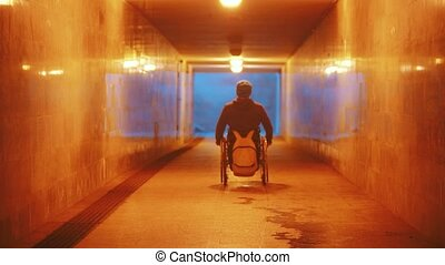 Disabled man in wheelchair riding in the empty underpass. Mid shot