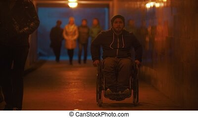 Disabled man in wheelchair riding in the underpass full of people. Mid shot
