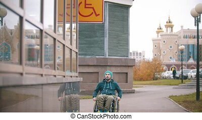 Disabled man in wheelchair sees the disabled sign and moving towards the special place. Mid shot