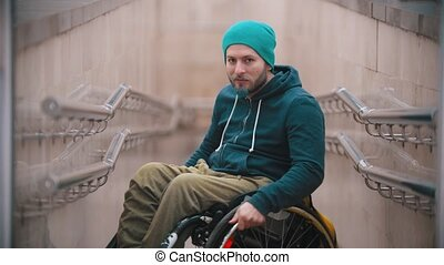 Disabled man in wheelchair smile and showing opportunities of his wheelchair. Mid shot