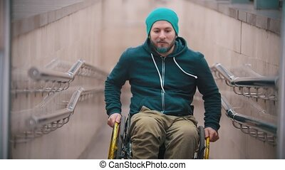 Disabled man in wheelchair smile and showing opportunities of his wheelchair - moving on the sides and leaning on the back wheels. Mid shot