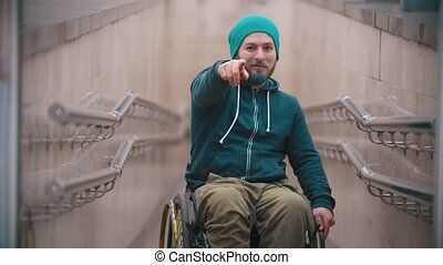 Disabled man in wheelchair smile waving his hand - showing ...