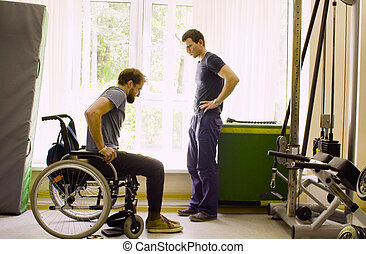 Disabled man in wheelchair talking with a doctor
