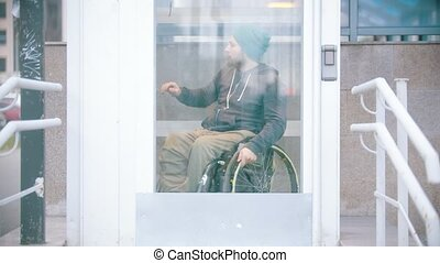 Disabled man in wheelchair using a special elevator for disabled people. Mid shot