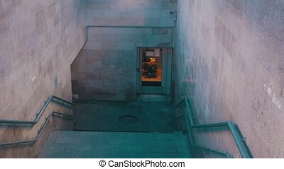 Disabled man in wheelchair using a special elevator for disabled people to get down in the underground crossing. Mid shot