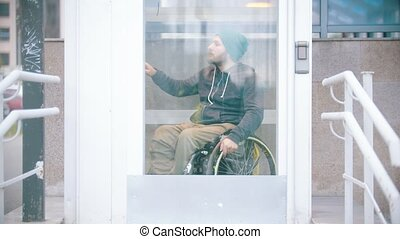 Disabled man in wheelchair using a special elevator for disabled people to get up from the underground crossing. Mid shot