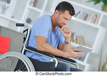 disabled man in wheelchair using digital tablet at home