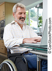 Disabled Man In Wheelchair Using Laptop At Home
