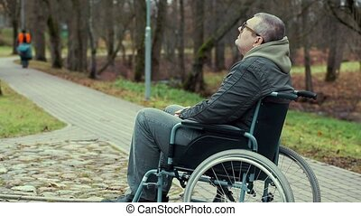 Disabled man in wheelchair waiting on path in the park