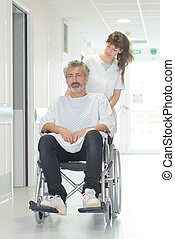 disabled man in wheelchair while a nurse is pushing him