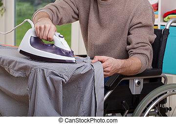Disabled man ironing shirt