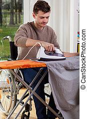 Disabled man ironing