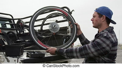 Disabled man looking at the wheel of his chair - Side view ...