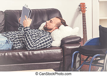 Disabled man lying on leather sofa