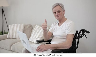 Disabled man on a wheelchair typing on the laptop - Smiling...