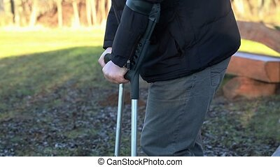 Disabled man on crutches at outdoor near benches