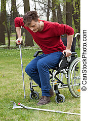 Disabled man on crutches in garden