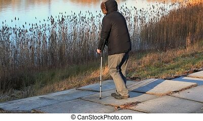 Disabled man on crutches near lake