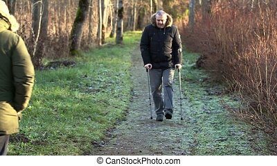 Disabled man on crutches on path