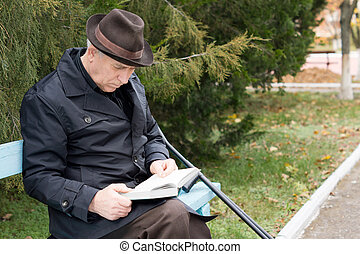 Disabled man on crutches reading in the park