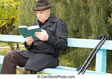 Disabled man on crutches sitting reading