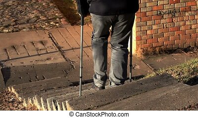 Disabled man on crutches walking down the stairs