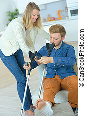 disabled man on crutches with help of a friend
