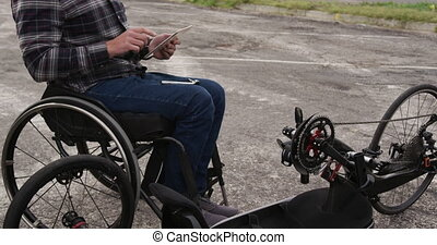 Disabled man on his touch pad after assembling parts of a ...