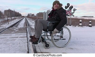 Disabled man on wheelchair near railway crossing