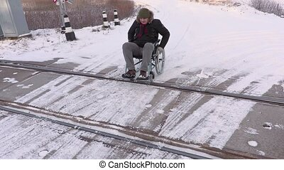Disabled man on wheelchair on railway crossing