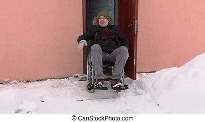 Disabled man on wheelchair talking near the door
