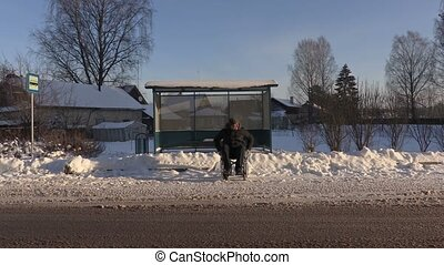 Disabled man on wheelchair waiting for bus in winter