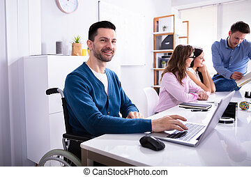 Disabled Man On Wheelchair Working In Office