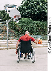 disabled man playing basketball in the city