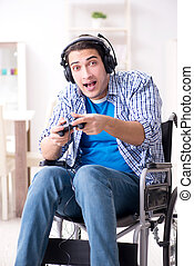 Disabled man playing computer games during rehabilitation