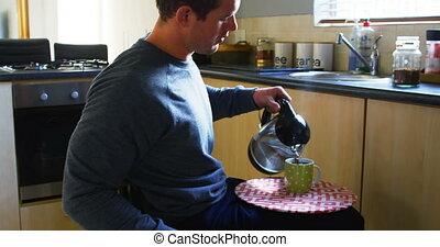 Disabled man preparing coffee in kitchen 4k