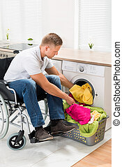 Disabled Man Putting Towels Into The Washing Machine - Young...