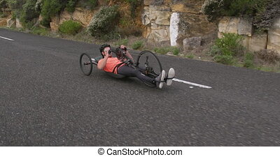 Disabled man riding a recumbent bicycle - Side view of a fit...