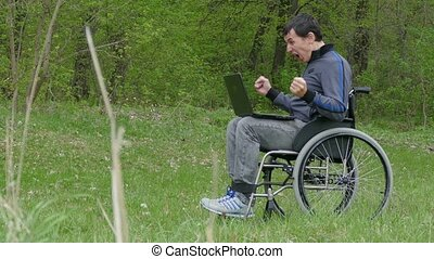 disabled man surprise success victory wheelchair with a laptop in a wheelchair working on nature green background
