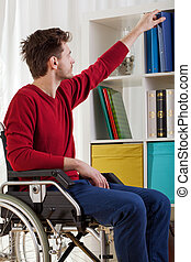Disabled man taking book
