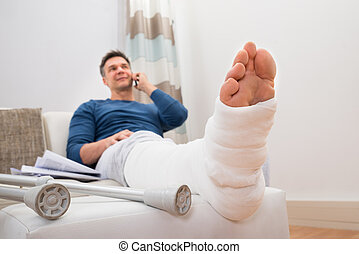 Disabled Man Talking On Cellphone - Man With Fractured Leg...